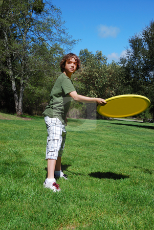 Teen Boy Throwing Frisbee stock photo, Teen boy throwing yellow frisbee with green grass, trees, and blue sky in the background. by Denis Radovanovic