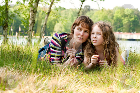 Mother and daugther relaxing in the grass stock photo, Mother and daughter have a happy time together by Frenk and Danielle Kaufmann