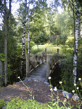 Wooden bridge stock photo, A wooden bridge leading to a garden by Alessandro Rizzolli