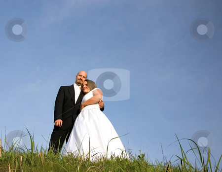Bride and Groom on Hill with Blue Sky stock photo, This lovely bride and groom are embracing and dreaming of their new life together.  Grass in the foreground and blue sky in the background. by Valerie Garner