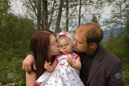 Mom and Dad Are Kissing Toddler Girl stock photo, This attractive young mom and dad are both kissing their toddler girl for a sweet family moment. by Valerie Garner