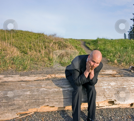Nervous Groom stock photo, This young groom is nervous and stressed about pre wedding gitters.  Shown here sitting on driftwood at a beach. by Valerie Garner
