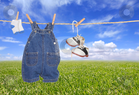 Baby Boy Child Clothes Hanging Outdoors stock photo, Baby Boy Child Clothes Hanging Outdoors Against a Bright Blue Sky by Katrina Brown