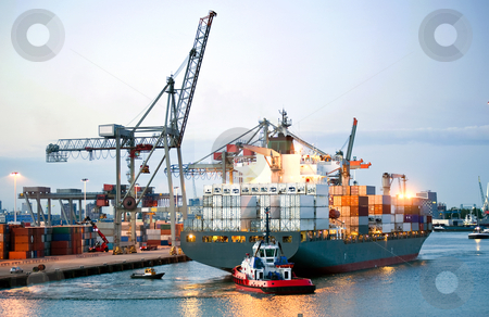 Manouvering container ship stock photo, Ah huge container ship being manouvered and reversed towards shore by pilots and tugboats by Corepics VOF