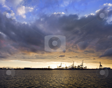 Sunset over harbor stock photo, A fiery sunset with dramatic clouds over a commercial harbor in the distance by Corepics VOF