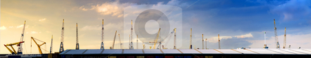 Cranes skyline stock photo, Panoramic image filled with a warehouse roof with cranes, sticking out like pins in a cushon with a natural gradient from yellow to blue in the sky due to the setting sun by Corepics VOF