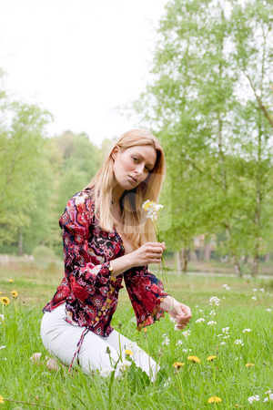 Sweet girl with a flower stock photo, Young blond girl collecting flowers in the grass by Frenk and Danielle Kaufmann