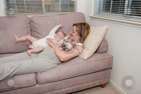 Relaxing on a sofa stock photo, Happy beautiful laughing mother lies on the sofa with her baby by Mariusz Jurgielewicz