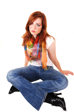 Tall red hair girl. stock photo, An pretty and tall teenager with bright red hair and colored scarf sitting on the floor of a studio. by Horst Petzold