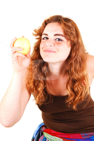 This apple is good. stock photo, Girl with yellow apple, long bright red hair in a close-up shoot and can  wait to eat the apple. by Horst Petzold