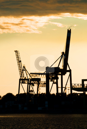 Harbor crane silhouettes stock photo, Silhouettes of two motionless, erect, idle harbor cranes against the setting sun by Corepics VOF