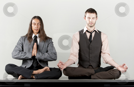 Two businessmen meditating stock photo, Two businessmen meditating on their office desk by Scott Griessel