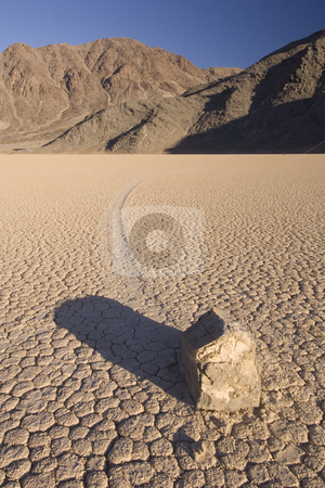 Death Valley stock photo, The phenomenon of the moving rocks at Death Valley Race Track Playa. The setting sun casts a shadow over the near by rock, still basking the mountains in the background in a warm glow by Corepics VOF