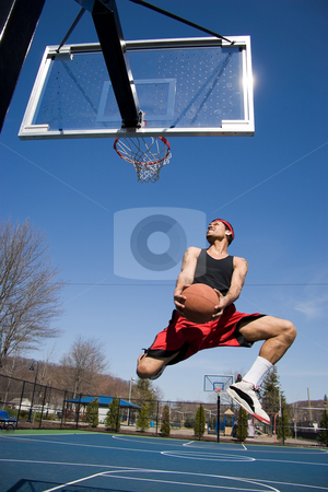 Man Playing Basketball stock photo, A young basketball player driving to the hoop. by Todd Arena