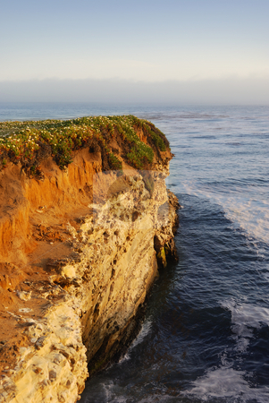 California Coast Cliff at Sunset stock photo, A California coast cliff at sunset with the Pacific Ocean in background and fog on the horizon. by Denis Radovanovic