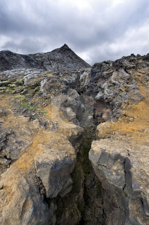 Volcanic Fissure stock photo, A glance in the volcanic Fissure of the 1984 eruption of the Krafla Volcanic system in Iceland. The solidified magma and lava is still hot, and provide a spectacular barren  view by Corepics VOF