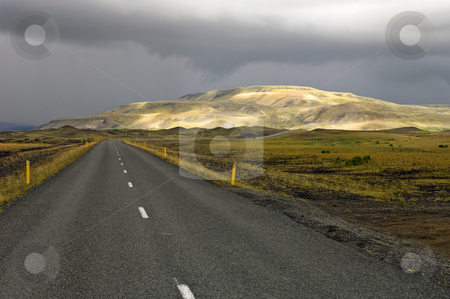 Sunlit Rhyolite Mountains stock photo, The sunlit Rhyolite Mountains of Myrdalur, Iceland, on a grim, overcast day, with the Number one ring road leading towards the volcanic mountain ridge by Corepics VOF