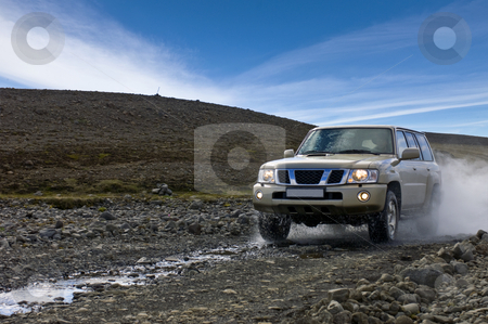 Off Road Driving stock photo, A big four by four car, emerging from a river, driving off over the uneven dirt road in Iceland by Corepics VOF