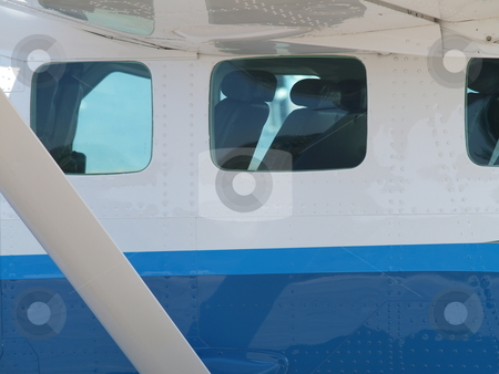 Aircraft 02  stock photo, Airplane section showing three windows and part of the wing by Jose .