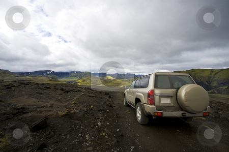 Driving in Landmannarlaugar stock photo, An all terrain car emerging from the grim lava fields into the meadows of the beautiful Landmannalaugar national park in Iceland by Corepics VOF