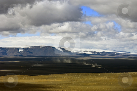 Sprengisandur stock photo, The trail of dust is the tell tale of an approaching car in the barren, empty Sprengisandur Highlands of Iceland, with the dominating Vatnajokull glacier and volcano in the background by Corepics VOF