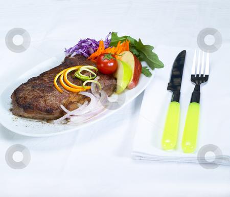 Beef ribeye steak stock photo, Fresh juicy beef ribeye steak grilled with lemon and orange peel on top and vegetables beside by Francesco Perre