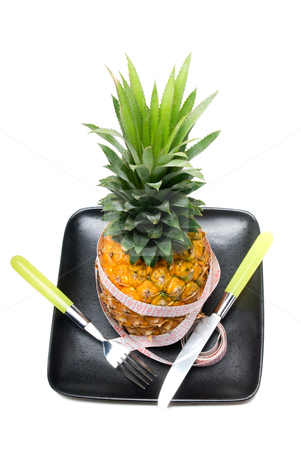 Pineapple stock photo, Pineapple on a black plate with tape meter,knife and fork isolated on white background by Francesco Perre