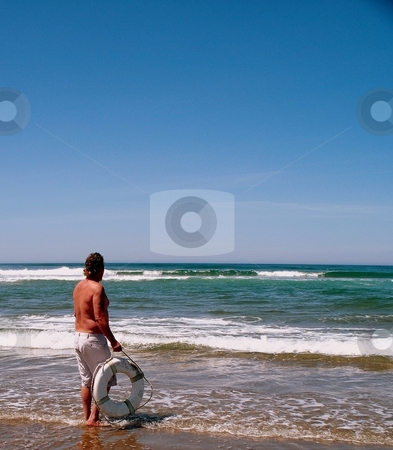 Man on the beach stock photo, Man on the beach holding a life ring by Carol Grimes