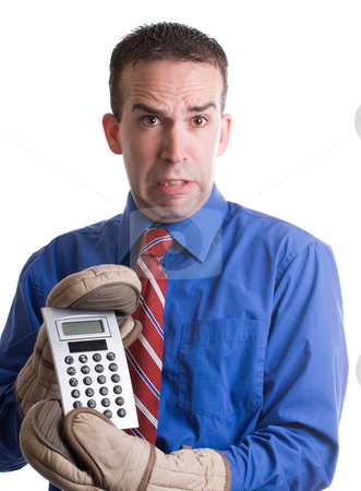 Economy stock photo, Concept image of an economy in trouble featuring a young banker holding onto his calculator with oven mitts, isolated against a white background by Richard Nelson
