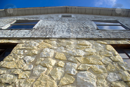 Old Stone Barn stock photo, Old Stone Barn with weathered siding on top by Steve Carroll