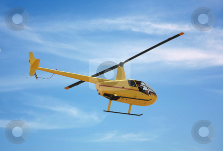 Yellow helicopter stock photo, Yellow helicopter flying in a natural blue sky background with a photographer on board by Stacy Barnett