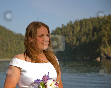 Pretty Young Bride Ocean & Blue Sky stock photo, This pretty Caucasian brunette bride is standing with the ocean and blue sky against the background as she's holding her bouquet of flowers. by Valerie Garner