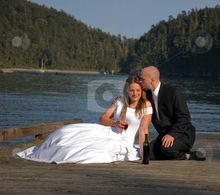 Sweet Bridal Kiss stock photo, This groom is giving his bride a sweet kiss as they share a glass of wine on a dock. by Valerie Garner