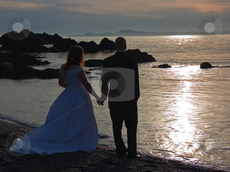 Wedding Couple at Sunset Holding Hands stock photo, This beautiful photo is a sunset of a wedding couple holding hands at the beach at sunset, for an ultra romantic shot. by Valerie Garner