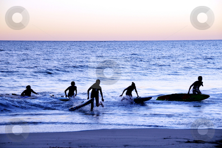 Silhouettes of teens  stock photo, Teens at the beach on surf boards by Laura Smith