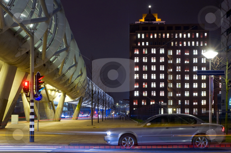 Night Traffic stock photo, A car accellerating when the traffic lights jumps to green in a business district with futuristic, modern buildings and an elevaated tram tube by Corepics VOF