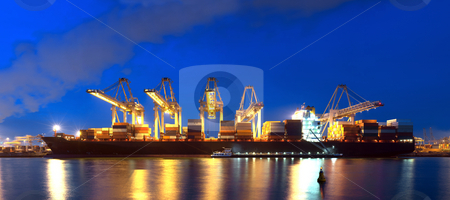 Container Ship panorama stock photo, An XXXL file of a container ship being unloaded at night at a busy commercial harbour, with a small trawler moored alongside. by Corepics VOF