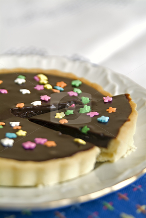 Chocolate Tart stock photo, Detail of a Chocolate Tart with colorful star candies by Noam Armonn