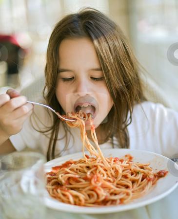 Child having spaghetti stock photo, Young girl eating spaghetti in restaurent by Noam Armonn