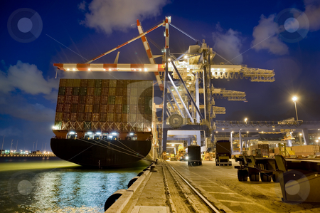 Cargo ship by night stock photo, Cargo ship at dock by night from behind by Noam Armonn