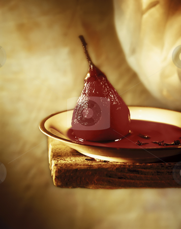 Red Pear in Wine stock photo, Red Pear cooked in Wine on a shelf with cloves by Noam Armonn