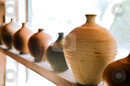 Pottery vases on shelf stock photo, Handmade pots/vases on a shelf at workshop by Noam Armonn