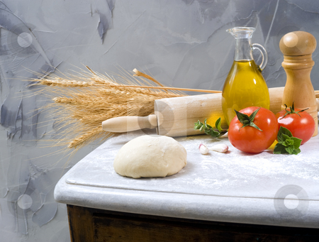 Baking ingredients stock photo, Dough, rolling-pin, olive oil tomatoes, oregano and garlic by Noam Armonn