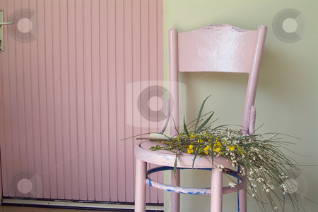 Old pink chair and flowers stock photo, Old pink chair and flowers in front of green wall and pink door. by Noam Armonn