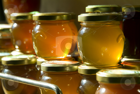 Honey jars on a shelf stock photo, Many honey jars on a shelf in a warehouse by Noam Armonn