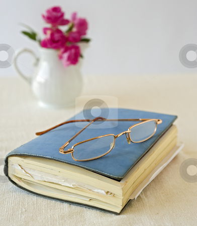 Book and glasses stock photo, Closed notebook and old glasses by Noam Armonn