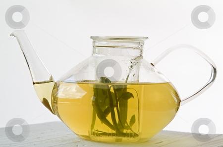 Glass Teapot with Herbal Tea stock photo, Glass Teapot with Herbal Tea on white wooden surface by Noam Armonn