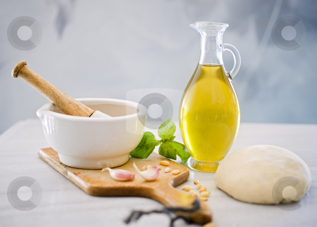 Baking ingredients stock photo, Dough, mortar and pestle, olive oil, bazil and garlic by Noam Armonn