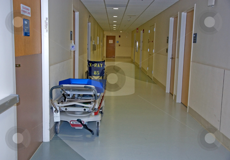Hospital Gurney & Wheelchair in Hallway stock photo, This medical scene features a gurney and wheel chair in a medical setting hallway. by Valerie Garner