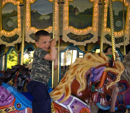 Boy Riding A Carousel Merry Go Round stock photo, This little boy is riding a carousel merry go round and hanging on tightly to the pole. by Valerie Garner